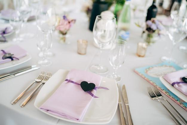 Bruiloft eettafel receptie witte vierkante borden op een ronde tafel met roze lappen servetten met een