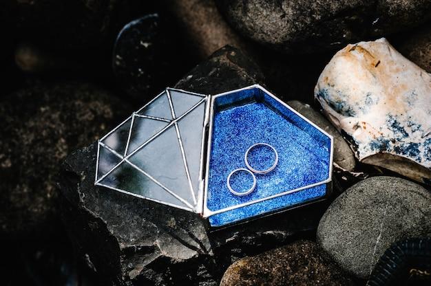 Bruiloft gouden zilveren verlovingsringen liggen in een glasvormige metalen doos in de vorm van een diamant