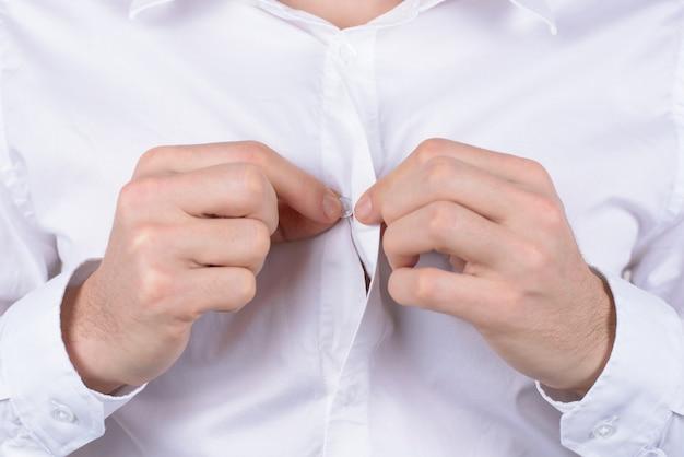 Bruiloft huwelijk voorbereiding concept. bijgesneden close-up foto van sierlijke serieuze heer die kleine knop aanraakt met vingers geïsoleerde grijze achtergrond gray