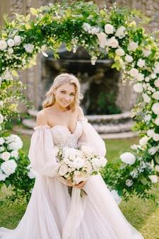 Bruiloft in een oude wijnmakerij villa in toscane, italië. portret van een bruid in de buurt van een ronde boog van bloemen. het decor voor de huwelijksceremonie.