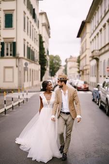 Bruiloft in florence, italië. multi-etnisch bruidspaar. afro-amerikaanse bruid in een witte jurk en blanke bruidegom in een hoed lopen langs de weg tussen auto's.