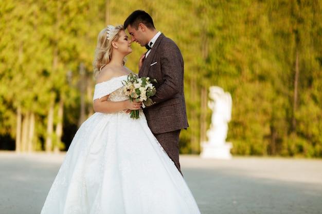 Bruiloft in het kasteel. stijlvol en mooi. princess's jurk. weelderige witte jurk en sluier. bruid is een brunette. de bruidegom in een zwart pak. een stel loopt in het park op het kasteelterrein.