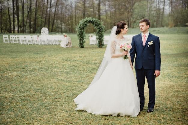Bruiloft in het voorjaar. ceremonie buiten. een boog van echte bloemen. de bruid en bruidegom kijken elkaar aan.