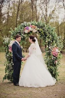 Bruiloft in het voorjaar. ceremonie op straat. een boog van echte bloemen. de bruid en bruidegom kijken elkaar aan.