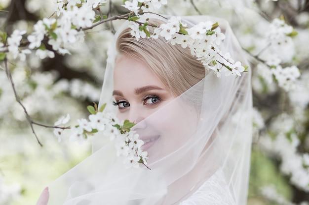 Bruiloft. jonge mooie bruid in witte jurk en sluier staande tussen bloesem bomen