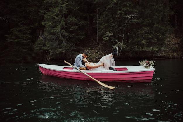 Bruiloft kus op de retro boot. bruid en bruidegom zitten in roze boot drijvend op het meer.