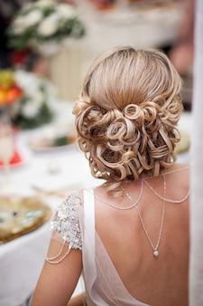 Bruiloft, mode en schoonheid - de bruid met een stijlvol kapsel in een prachtige trouwjurk met open rug. achteraanzicht.