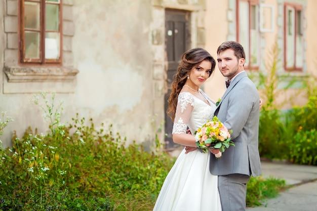 Bruiloft: mooie bruid en bruidegom in het park op een zonnige dag