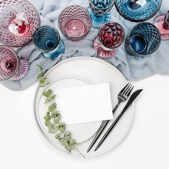 Bruiloft of feestelijke tafel setting. borden, wijnglazen en bestek met grijs decoratief textiel op witte achtergrond. mooie regeling.