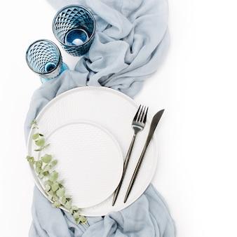 Bruiloft of feestelijke tafel setting. borden, wijnglazen, kaarsen en bestek met grijs decoratief textiel op witte achtergrond. mooie regeling.