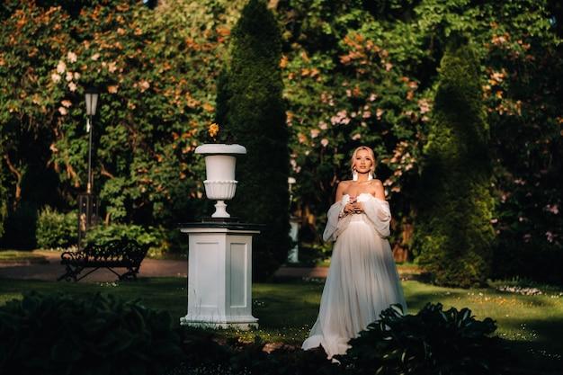 Bruiloft oorbellen aan een vrouwelijke hand, ze neemt de oorbellen, de bruidsprijzen, ochtendbruid, witte jurk, oorbellen dragen