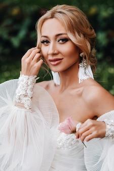 Bruiloft oorbellen aan een vrouwelijke hand, ze neemt de oorbellen, de bruidsprijzen, ochtendbruid, witte jurk, oorbellen dragen.