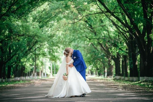 Bruiloft, paar bruid en bruidegom kussen in park met zeer grote bomen.