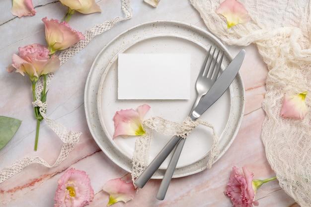 Bruiloft plaatskaart liggend op een keramische plaat op een marmeren tafel versierd met bloemen en linten