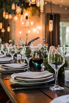 Bruiloft receptie tafel met edison bollen en decor van groen.