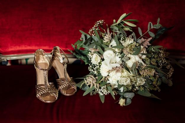 Bruiloft set bruidsboeket en gouden sandalen schoenen op rode klassieke sofa. bruid ochtend voorbereiding