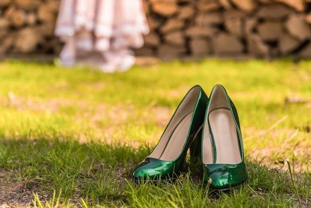 Bruiloft smaragdgroene bruidsmeisjesschoenen op het groene gras op de achtergrond van de jurk