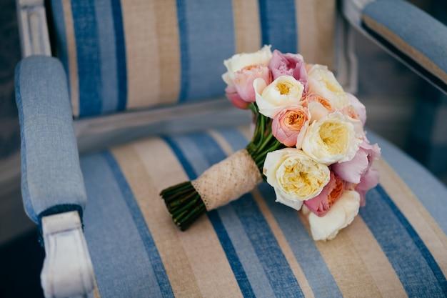 Bruiloft symbool. prachtig bruidsboeket ligt op vintage fauteuil, voorbereid voor speciale gelegenheid.