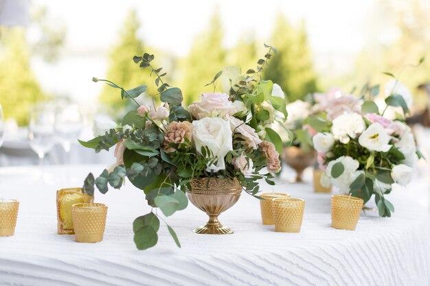 Bruiloft tabel instelling versierd met verse bloemen in een koperen vaas. bloemisten bruiloft. bankettafel voor gasten buiten met uitzicht op de groene natuur. boeket met rozen, eustoma en eucalyptusbladeren