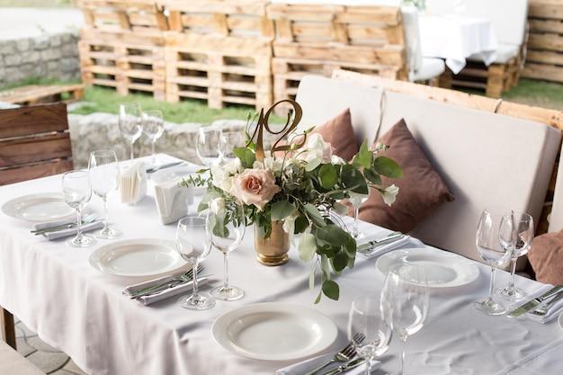 Bruiloft tabel instelling versierd met verse bloemen in een koperen vaas. bruiloft bloemisterij. bankettafel voor gasten buiten met uitzicht op de groene natuur. boeket met rozen, eustoma en eucalyptusbladeren