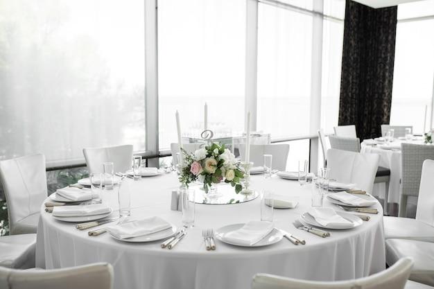 Bruiloft tabel instelling versierd met verse bloemen.
