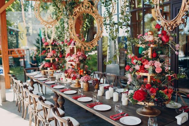 Bruiloft tafel bloemen met fruit en bessen decor in rood wit roze groene kleuren.