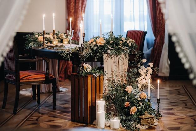 Bruiloft tafeldecoratie met bloemen op de tafel in het kasteel, tafeldecoratie voor het diner bij kaarslicht. diner met kaarsen.