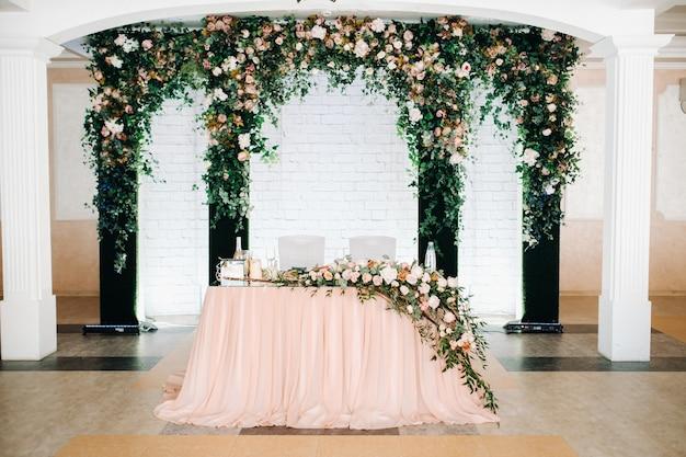 Bruiloft tafeldecoratie met bloemen op de tafel in het restaurant tafeldecor voor diner bij kaarslicht.