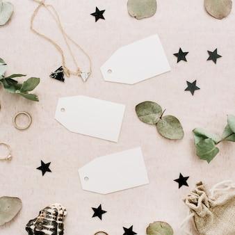 Bruiloft tags met eucalyptus takken, ringen, sterren en accessoires op lichtroze achtergrond. platliggend, bovenaanzicht