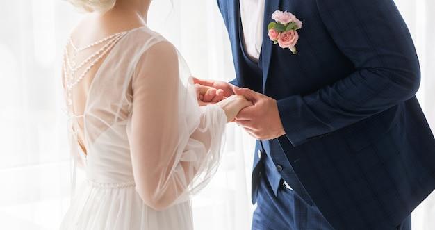 Bruiloft thema, hand in hand jonggehuwden. de bruid en bruidegom houden elkaars hand vast