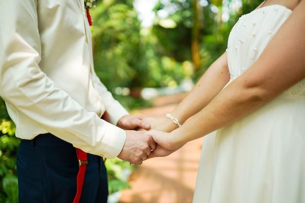 Bruiloft thema, hand in hand jonggehuwden in warme zomerdag