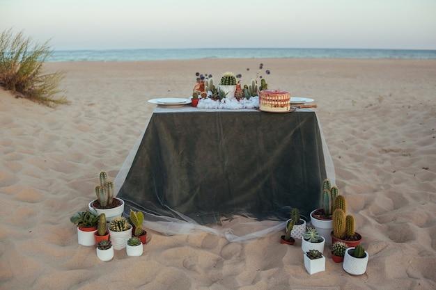 Bruiloft versierde tafel met vetplanten op het strand. bruidstaart met kopercrème en vetplanten. bruiloft decoratie. ceremonie op het strand