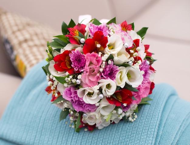 Bruiloft verzadigd boeket van verschillende bloemen van de bruid op de sofa