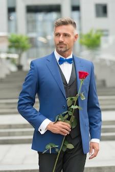Bruiloft voorbereiding. valentijnsdag concept. sexy man smoking en vlinderdas. wees voor altijd mijn vrouw. bezoek privé feest. elegante zakenman die rode roos voorstelt. romantiek en liefde. dag van zijn huwelijk.