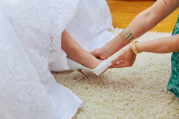 Bruiloft voorbereiding. vriendinnen van de bruid helpen haar in mijn schoenen trouwschoenen