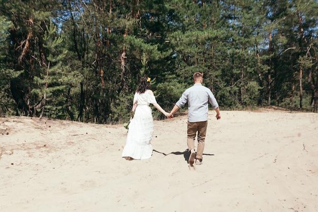 Bruiloft wandeling in het dennenbos. bruidspaar in het bos. mooie bruid en bruidegom op wandeling