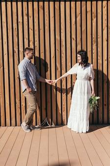 Bruiloft wandeling in het dennenbos. zonnige dag. bruidspaar in het bos. mooie bruid en bruidegom op een wandeling. witte trouwjurk. boeket van pioenrozen en hortensia's.