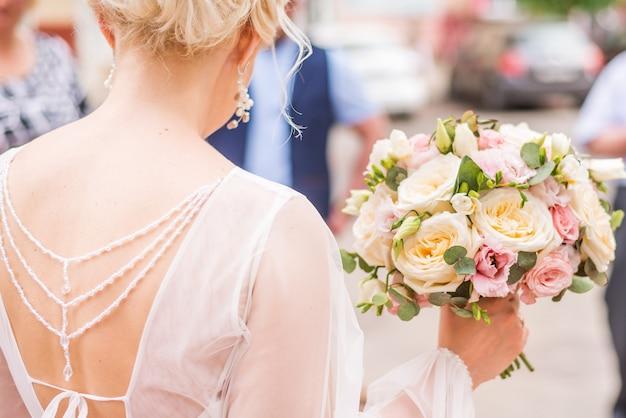 Bruiloftsboeket met crème en roze rozen in de handen van de bruid.
