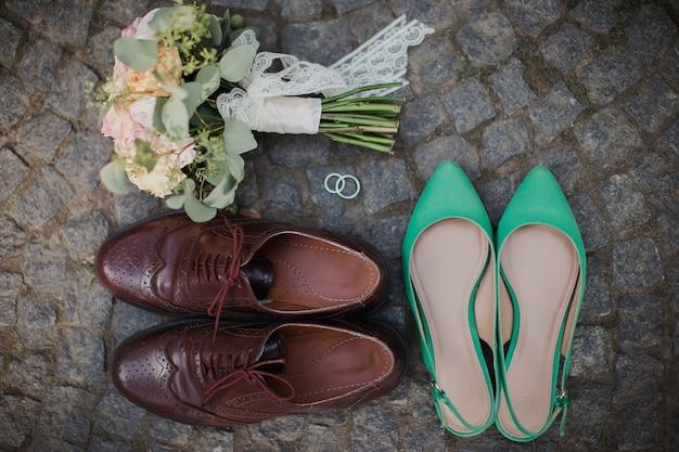 Bruiloftsboeket, schoenen, ringen op de stenen tegel.