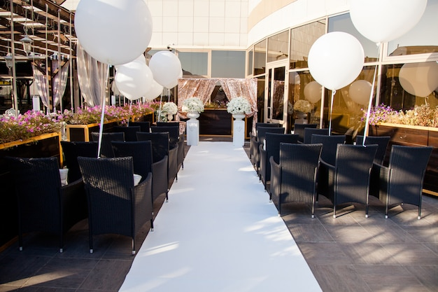 Bruiloftsdecor, stoelen voor gasten, trouwringen en enorme witte ballonnen