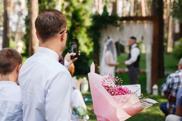 Bruiloftsgast neemt foto bruid en bruidegom buiten in de zomer man neemt trouwfoto op telefoon