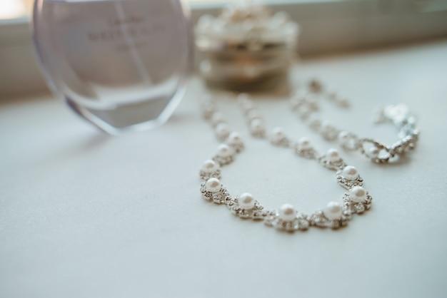 Bruiloftsjuwelen en de fles van het parfum. bruiloft accessoires