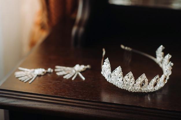 Bruiloftskroon voor de bruid en oorbellen liggen op het latwerk.