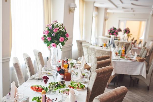 Bruiloftstafel die versierd is met bloemstukken