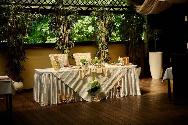 Bruiloftstafel in rustieke stijl, decoraties gemaakt van hout en wilde bloemen geserveerd op de feesttafel