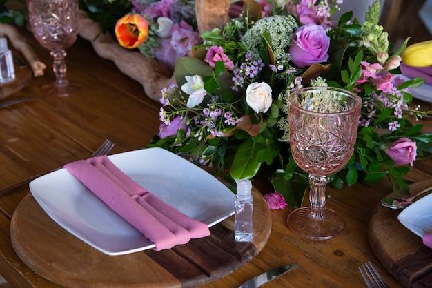 Bruiloftstafel met houten borden en roze tafelkleed versierd met verse bloemen en decoratieve glazen