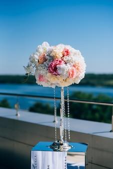 Bruiloftsversieringen van bloemen en een huwelijksboog voor de ceremonie