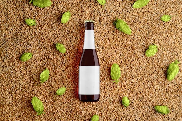 Bruin bierglas bottlle sjabloon op tarwe en enkele hopbellen met grijs label. bovenaanzicht. mockup klaar voor uw showcase.