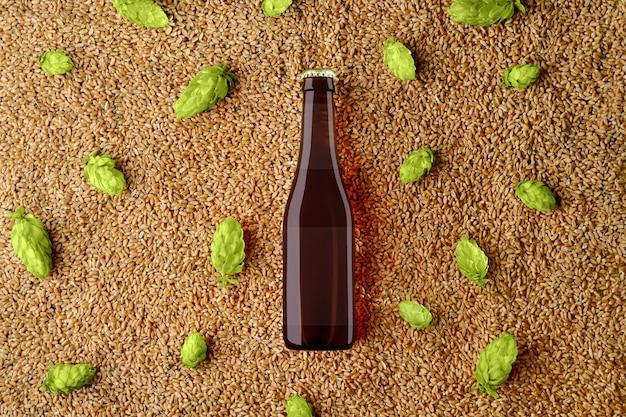 Bruin bierglas fles sjabloon op tarwe en enkele hopbellen met doorschijnend etiket. bovenaanzicht. mockup klaar voor uw showcase.
