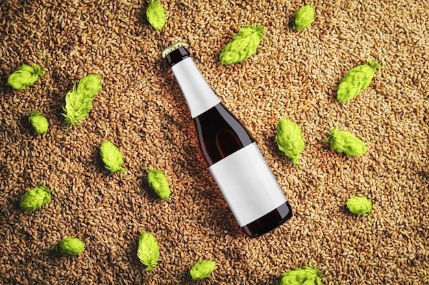 Bruin biermodel met glazen fles met diagonale plaatsing op tarwe en enkele hopbellen met grijs label. sjabloon klaar voor uw showcase.